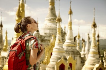 Hiker traveling with backpack and looks at Buddhist stupas. Tours and activities market.