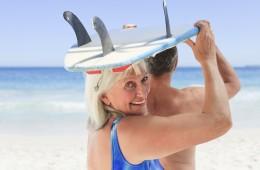 Senior couple with their surfboard