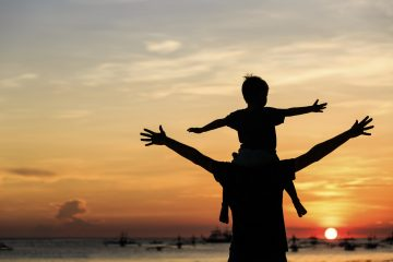 father and son playing on sunset beach