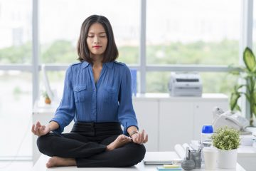 How to achieve mindfulness at work? Asian businesswoman sitting on table and meditating.