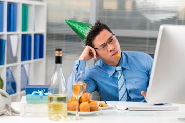 Sad Asian manager in a party hat looking at the computer screen