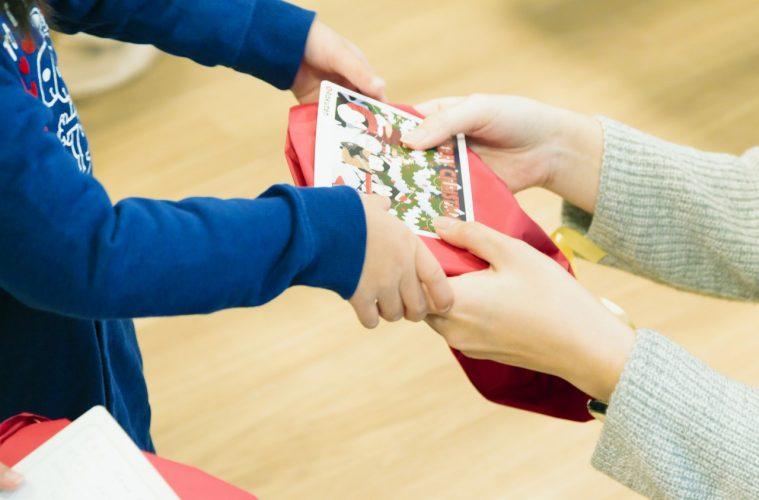 A Rakuten employee gives a present to a child