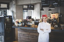 Smiling asian female cuisinier is posing for a portrait standing next to a bar counter with food and drinks. Image contains plenty of copy space.