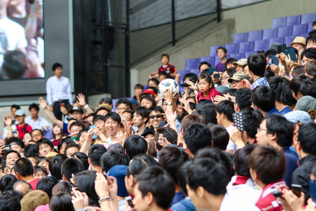 Vissel Kobe fans reach for ball kicked by Andres Iniesta at special welcome event at Noevir Stadium