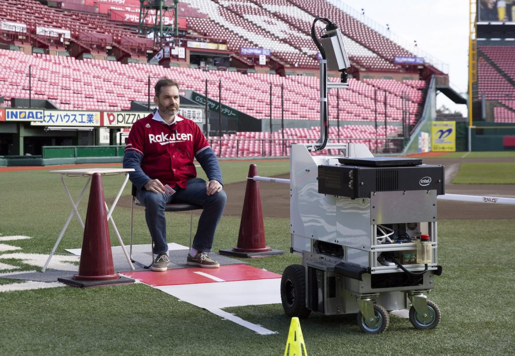 An unmanned delivery robot brings a package to a member of staff on the field.