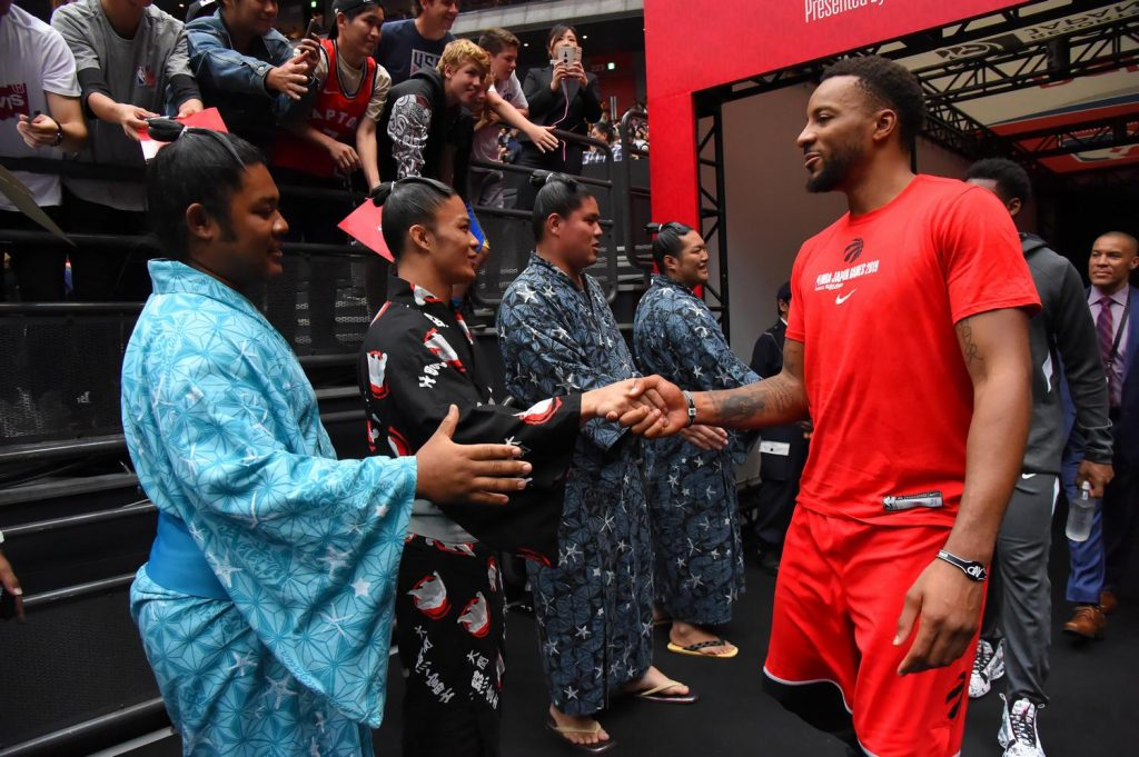 Raptors guard Norman Powell greets sumo wrestlers on his way out of the lockers.