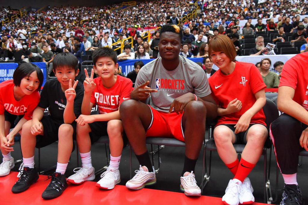 Rockets center Clint Capela and former W.League champion Mao Okada sit with young fans.